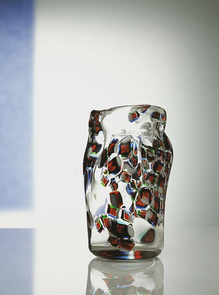 Vaso, 1960 Vaso a forma di corpo di donna in vetro incolore con murrine irregolari di colore rosso, blu, verde e lattimo; cm 13,5 (diam.) x 22,7